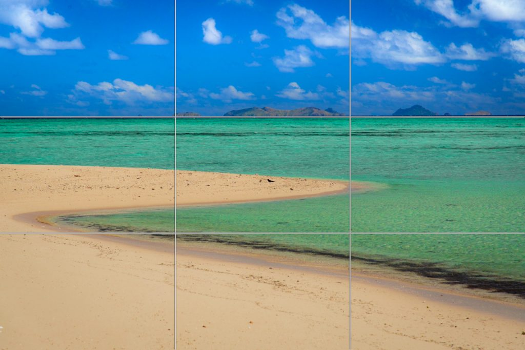 Rule of Thirds grid overlayed an image of a beach landscape, with islands on the horizon line